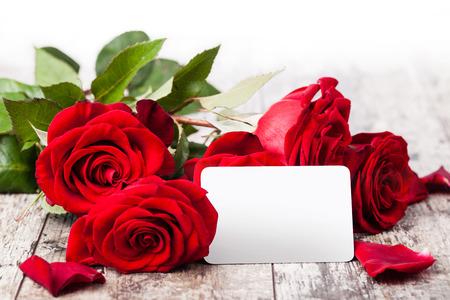 rosas rojas: Rosas rojas con una etiqueta de regalo en blanco en un woodwn Foto de archivo