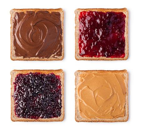 Tostada con el chocolate, mantequilla de maní y mermelada. Aislado en un fondo blanco