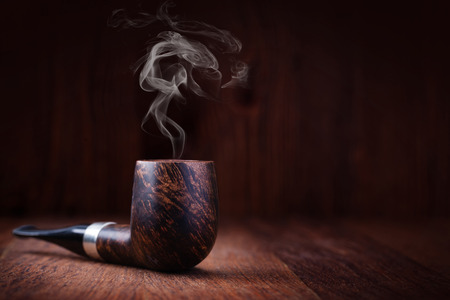 pipe: Smoking pipe on a wooden table Stock Photo