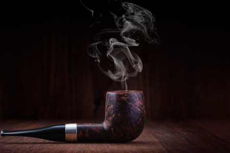 Smoking pipe on a wooden table Stock Photo