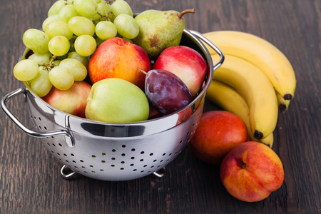 Fresh fruits in colander on wooden table.