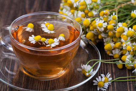 chamomile tea: Cup of medicinal chamomile tea on a wooden