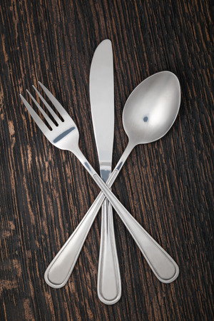 fork and knife: Fork, spoon and knife isolated on a wooden table