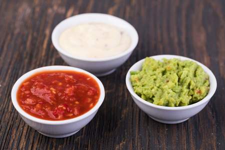 Bowls with sauces on white background Stock Photo