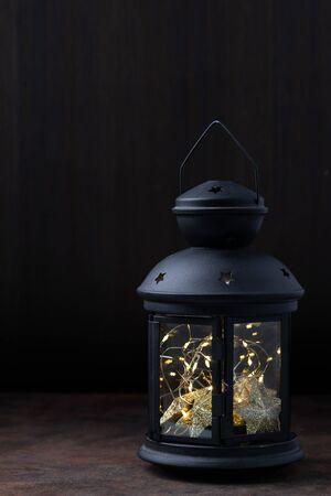 fairy lights inside vintage lantern on wooden table Imagens