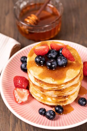 Pancakes with fresh strawberries, blueberries and syrup