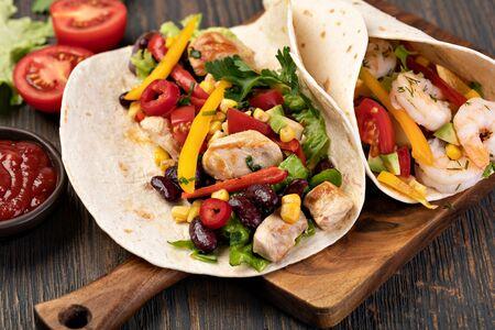 Burrito mit Gemüse und Tortilla auf einem Holztisch Standard-Bild