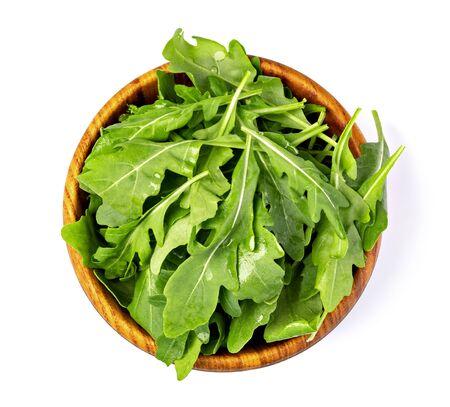 Fresh green arugula leaves on wooden bowl isolated on white background