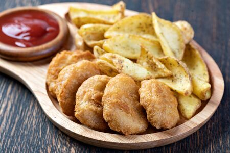 Tasty fried nuggets and potatoes on a table