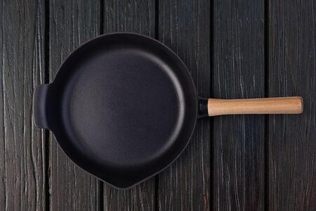 Empty frying pan on wooden culinary background