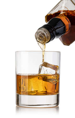 whiskey poured into a glass from a bottle isolated on a white background