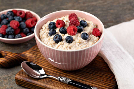 prepared oatmeal with berries on a wooden table Zdjęcie Seryjne