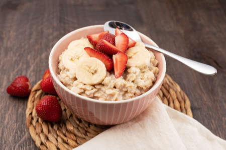 prepared oatmeal with fruits and berries on a wooden table