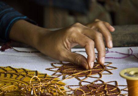 craftman: Hand detail of a Burmese woman at work sewing beads