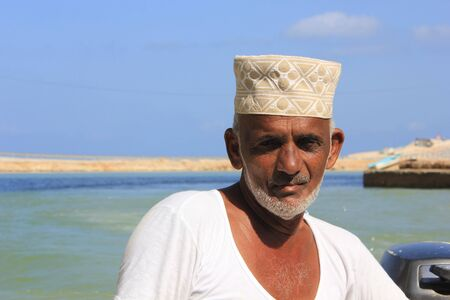 he is a traditional: Sur, Oman, October 23, 2013: Omani fisherman at work. He is wearing the traditional omani hat, the kumma, used during unofficial time.