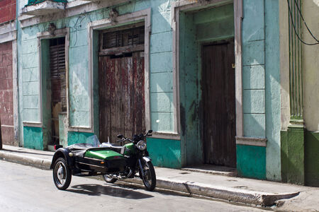 colonic: Green vintage sidecar in a cuban street. In Matanzas, west side from Havana in Cuba, an old fashioned sidecar is parket in froont of a colonial building.