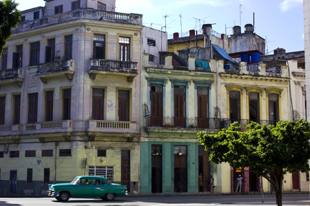 The colours oh Havana: palaces, car, life.Capture oh a typical colonial Havana building, while an old-fashioned car cross the street. Colours, tree, people, all in one shot.