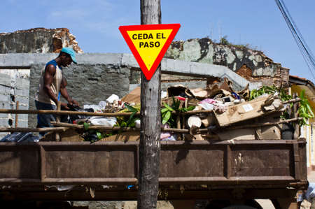 precedence: Trinidad, Cuba: Priority Road sign in the street of Trinidad, and a man working on a garbage truck