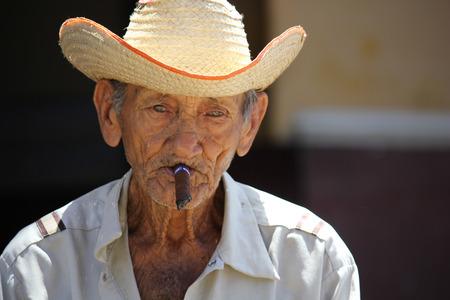 Trinidad, Cuba, August 19, 2012. An old man smoking a typical cuban cigar.