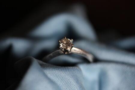 ring engagement: Anillo de compromiso en un tejido azul. Un diamante para un para siempre amor. De cerca
