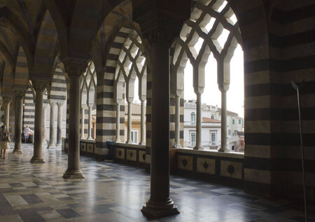 predominantly: Amalfi, Italy, August 11, 2014: Amalfi Cathedral  (it.Duomo di Amalfi), external colonnade. The church is dedicated to the Apostle Saint Andrew. Predominantly of Arab-Norman Romanesque architectural style Editorial