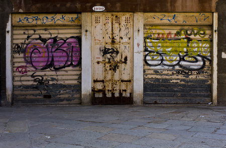 Venice, Italy, June 4 2014: Glimpse of an unknown Venice. Unusual view of the city and its little streets. A garage with a mural