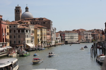 navigating: view of Venice from Ponte degli Scalzi, looking at the Grand Canal below, with all the traditional Venetian boats navigating and San Simeone Piccolo church cupola