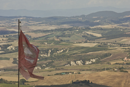 montalcino: Montalcino, Italy: Montalcino flag waving from the tower of the Castle, overviewing the amazing Tuscany landscape