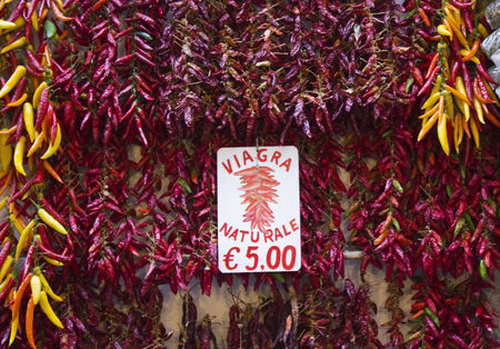 aphrodisiac: Amalfi, Italy: Red Hot Chili peppers display in an outdoor market in Amalfi, with the script natural viagra for its aphrodisiac properties