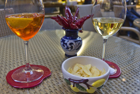 Amalfi, Italy: Happy hour in Amalfi. Two glass, one with a spritz and the other with white wine, with the traditional Amalfi ceramics and red hot chilli pepper