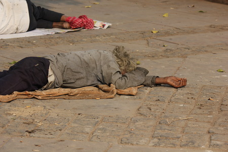 handout: Delhi, India: Very poor homeless person asking charity lying down in the street Editorial
