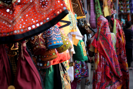 PUSHKAR, INDIA: Street market in India, with colorful dressed and bags hung on the stand and Indian women in the background