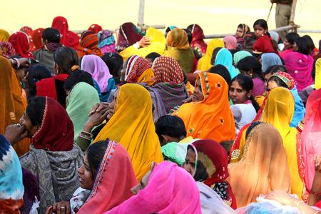 exhibition crowd: Pushkar, India: Folla di persone alla fiera di Pushkar, nello stato indiano del Rajasthan, in attesa di una mostra. Molti bella donna saree colorato.
