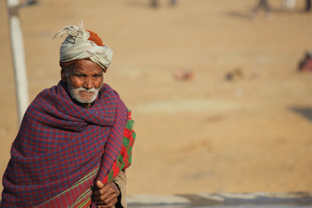 white beard: PUSHKAR, INDIA: Old Indian man with turban and white beard, covered with a blanket,  walking in Pushkar