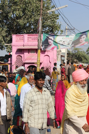 indian fair: Pushkar, India: Indian people walking in the street of Pushkar during the Camel Fair, with a pink building in the background.
