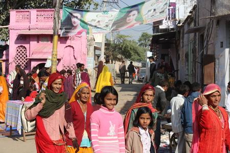 personnes qui marchent: Pushkar, Inde: les Indiens marchant dans la rue de Pushkar pendant la Foire Camel, avec un b�timent rose en arri�re-plan.