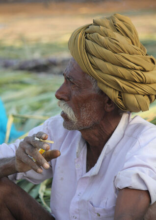 turban: PUSHKAR, INDIA:  Indian man with green turban smoking a cigarette sit on the grass in Pushkar