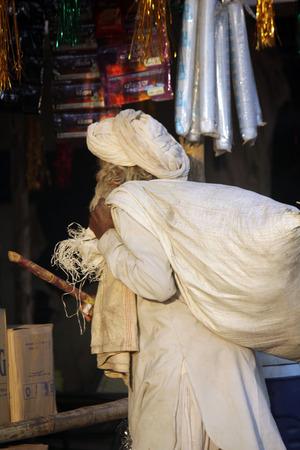 sackful: PUSHKAR, INDIA: Indian senior man, white dressed, walking with a cane and a big sack on hos shoulder, at Pushkar Fair in India