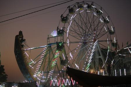 nightview: PUSHKAR, INDIA: Pushkar fair at sunset. View of the Ferris wheel illuminated in the sky Editorial