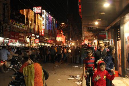 personnes qui marchent: DELHI, INDE: New Delhi par nuit. Vue de nuit d'une rue commer�ante illumin� avec des gens tout autour de la marche