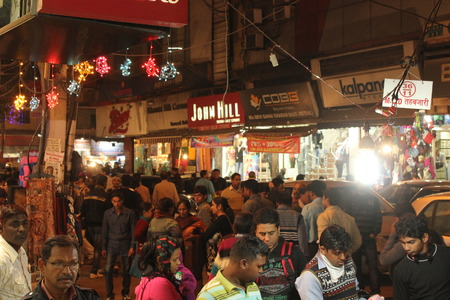 new delhi: DELHI, INDIA: New Delhi by Night. Night view of a shopping street illuminated with people walking all around