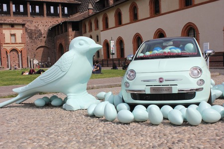 sforzesco: MILAN, ITALY - APRIL 12 2012: Inside the Milan Sforza Castle, plaastic birds on the floor with a Fiat 500 car, colorful plastic swallows by Cracking Art group.