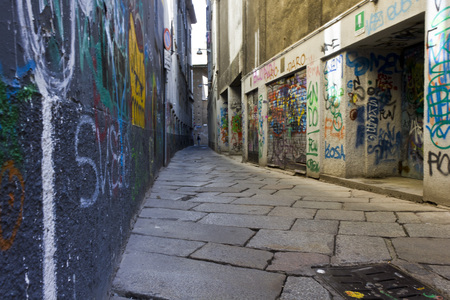 characterized: MILAN, ITALY - MAY 9: Via Bagnera, a narrow street in the heart of the city of Milan, characterized by murals throughout the wall, on May 9 2014 Editorial