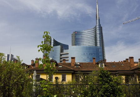 modernity: MILAN, ITALY: Milan between history and Modernity. Traditional milanese historic house in the foreground with the new modern glass building of Unicredit in the background Editorial