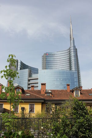 glass building: MILAN, ITALY: Milan between history and Modernity. Traditional milanese historic house in the foreground with the new modern glass building of Unicredit in the background Editorial