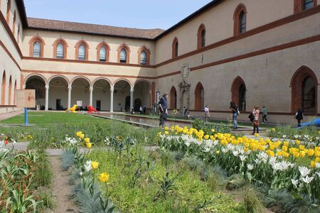 sforzesco: MILAN, ITALY - APRIL 12: Courtyard of Milan Sforza Castle, with yellow and white poppies and people walking around it on Aprile 12 2014