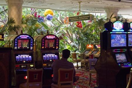 tragamonedas: LAS VEGAS, EE.UU. - 05 de agosto 2013: Wynn Las Vegas del casino con la gente que juega en las m�quinas tragaperras en 06 de agosto 2013 Editorial