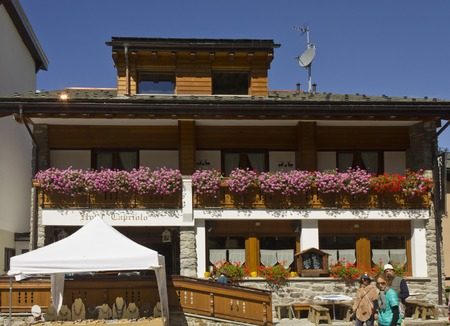 breakfast hotel: MADESIMO, ITALY - AUG 21 2014: Capriolo bed and breakfast hotel and restaurant in Madesimo city centre in summer, with flowers.