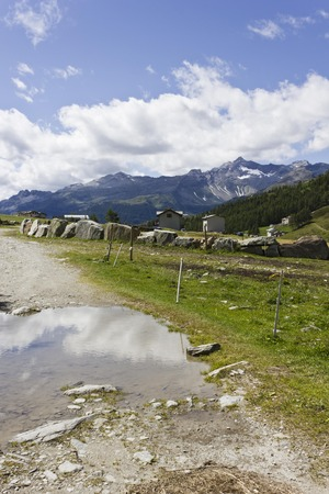 mountain peek: MADESIMO, ITALY - AUG 21 2014: Mountain path in Madesimo valley floor at summer, with mountain reflection in the puddle and stone house and glacier  Editorial