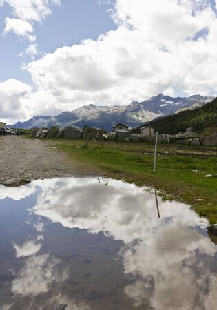 mountain peek: MADESIMO, ITALY - AUG 21 2014: Mountain path in Madesimo valley floor at summer, with cloud reflection in the puddle and stone house and glacier